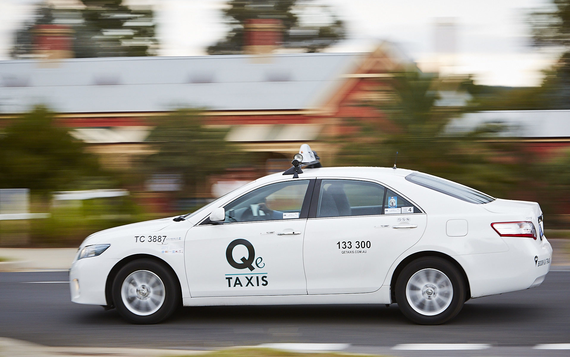 Q e Taxis driving past Queanbeyan Railway Station